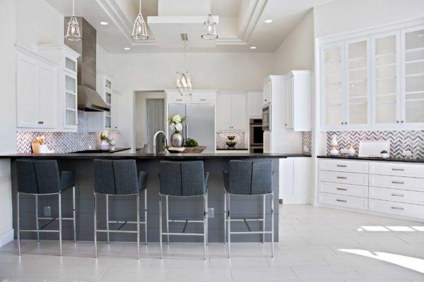 Bright White Modern Kitchen With Chevron Backsplash and gray countertops